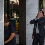 A woman withdraws money from a bank cash machine from a National Bank branch while another reacts behind her in central Athens on Saturday, June 27, 2015. Anxiety over Greece's future swelled on Saturday, with people queuing outside banks to withdraw cash, after Prime Minister Alexis Tsipras' call to have the people vote on a proposed bailout deal increases the risks that the country might fall out of the euro. (AP Photo/Daniel Ochoa de Olza)