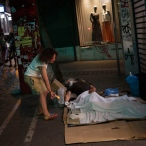 A woman leaves a croissant next to a sleeping man living in the streets of central Athens, Thursday, June 25, 2015. The ECB approved a request from Athens to increase the amount of emergency liquidity Greek lenders can tap from the country's central bank. Worried Greeks have been withdrawing their money from their country's banks, fearing the imposition of restrictions on banking transactions. An estimated more than 4 billion euros ($4.5 billion) left Greek banks last week. (AP Photo/Daniel Ochoa de Olza)