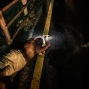 In this May 29, 2015 photo, a police officer shines a flashlight on a severely injured man in San Salvador, El Salvador. The fast response unit was responding to a hit and run call, but police speculated from the man's deep upper body wounds, he had more likely been tortured and then dumped on this roadside. (AP Photo/Manu Brabo)