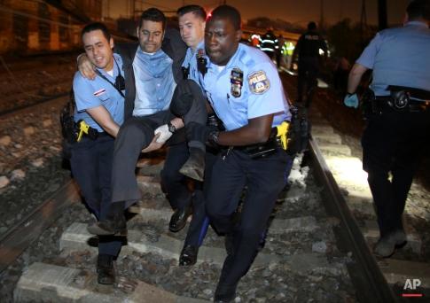 Emergency personnel help a passenger at the scene of an Amtrak train wreck, Tuesday, May 12, 2015, in Philadelphia. (AP Photo/Joseph Kaczmarek)