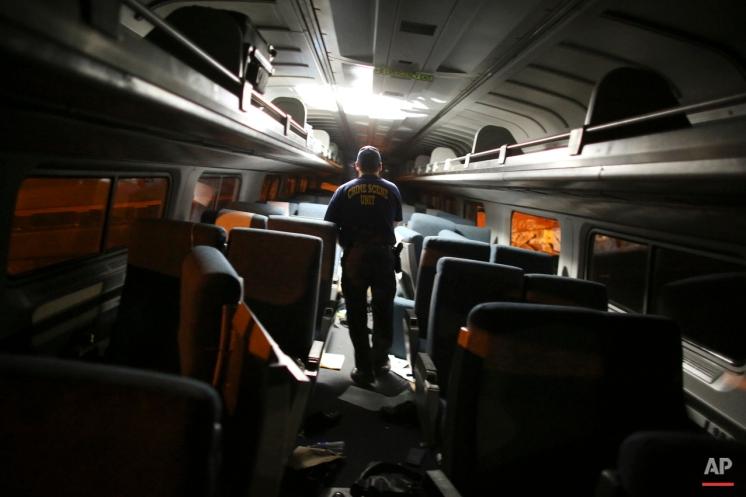 A crime scene investigator looks inside a train car after an Amtrak train wreck, Tuesday, May 12, 2015, in Philadelphia. (AP Photo/Joseph Kaczmarek)