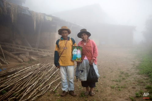 In this March 15, 2015 photo, Julio Galvez and his wife Rufina Miguel, pose for a picture holding a portrait of their late son Yuri Galvez, outside their home, in La Mar, province of Ayacucho, Peru. The 25-year-old university student had gotten his father's permission to haul coca in a backpack to pay for his agronomy studies, his mother said. Yuri was found face-up on a mountain trail, with bullet wounds to his head, stomach and arm, in a March 2013 cocaine smuggling trip. (AP Photo/Rodrigo Abd)