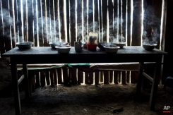 In this March 15, 2015 photo, steaming bowls of chicken soup on a table set for a special meal marking the second death anniversary of cocaine backpacker Yuri Galvez, in La Mar, province of Ayacucho, Peru. Galvez, 25, was found dead two years to the date, while taking part in a cocaine smuggling trip with other backpackers. (AP Photo/Rodrigo Abd)