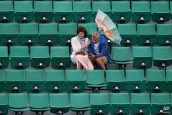 The wind pulls at the umbrella of a spectator as weather conditions suspended the fourth round match between France's Alize Cornet and Ukraine's Elina Svitolina at the French Open tennis tournament at Roland Garros stadium, Paris, France, Sunday, May 31, 2015. (AP Photo/David Vincent)
