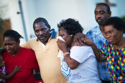 Gary and Aurelia Washington, center left and right, the son and granddaughter of Ethel Lance who died in a shooting at Emanuel AME Church, leave a sidewalk memorial in front of Emanuel AME Church comforted by fellow family members, Thursday, June 18, 2015, in Charleston, S.C. (AP Photo/David Goldman)