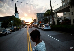 A woman crosses the street on her way to visit a sidewalk memorial to the Emanuel AME Church shooting victims as the sun rises next to the church's steeple, Sunday, June 21, 2015, in Charleston, S.C. Congregation members say the historic black church where nine people were killed is going to re-open for Sunday morning service. (AP Photo/David Goldman)