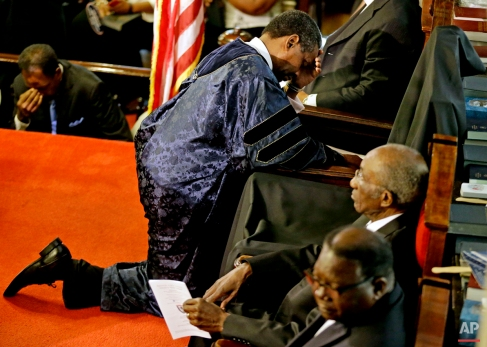 Rev. Norvel Goff prays at the empty seat of the Rev. Clementa Pinckney during the first service at the Emanuel A.M.E. Church, Sunday, June 21, 2015, in Charleston, S.C., since a mass shooting claimed the lives of Pinckney and eight others four days earlier. (AP Photo/David Goldman)