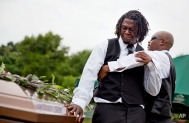 Brandon Risher, left, is pulled away by a friend as he cries over the casket of his grandmother, Ethel Lance, following her burial service, the first one for the nine people killed in the shooting at Emanuel AME Church, Thursday, June 25, 2015, in Charleston, S.C. (AP Photo/David Goldman)