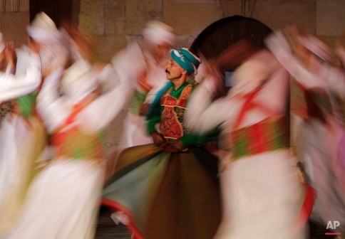 In this Saturday, May 30, 2015 photo, whirling dervishes members of the Al-Tannura Egyptian Heritage Dance Troupe Al-Tannoura Egyptian Heritage Dance Troupe spin during a performance at the 15th century Ghouri Palace, in Cairo, Egypt. Religious devotion is at the heart of almost everything. (AP Photo/Amr Nabil)