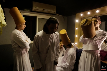 In this Thursday, April 23, 2015 photo, whirling dervish Sayed Abdel Basir, center, a member of the Al-Tannoura Egyptian Heritage Dance Troupe, prays inside a dressing room, before the group performs at the El Sawy cultural center in Cairo, Egypt. (AP Photo/Amr Nabil)