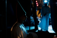 """In this Thursday, May 28, 2015 photo, whirling dervish Ali Taha, a member of the Al-Tannoura Egyptian Heritage Dance Troupe, waits backstage before a performance, at the El Sawy culture center in Cairo, Egypt. """"I'm ready to dance for free, especially with the Mawlawiyah dervishes,"""" said Taha. """"While whirling I feel like a white bird flying in the sky."""" (AP Photo/Amr Nabil)"""