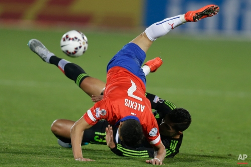 Chile's Alexis Sanchez falls over Mexico's Carlos Salcedo, bottom, during a Copa America Group A soccer match at El Nacional stadium in Santiago, Chile, Monday, June 15, 2015. The match ended in a 3-3 draw. (AP Photo/Natacha Pisarenko)