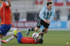 Chile's Charles Aranguiz, bottom, tackles Argentina's Lionel Messi, right, during the Copa America final soccer match at the National Stadium in Santiago, Chile, Saturday, July 4, 2015. (AP Photo/Ricardo Mazalan)