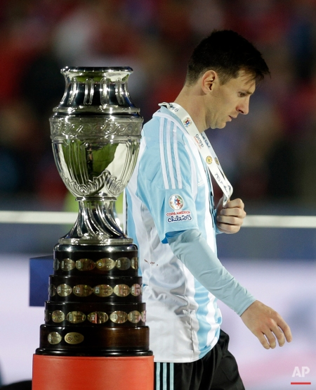 Argentina's Lionel Messi walks by the Copa America trophy after receiving the silver medal after the final game with Chile at the National Stadium in Santiago, Chile, Saturday, July 4, 2015. Chile goalkeeper Claudio Bravo made a save and striker Alexis Sanchez converted the winning penalty as host Chile defeated Argentina 4-1 in a shootout after a 0-0 draw in the Copa America final.(AP Photo/Natacha Pisarenko)