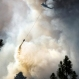 A helicopter dumps a load of water on the fast-moving Fish Lake Fire near Scribner Road, Wednesday, June 17, 2015. (Colin Mulvany/The Spokesman-Review, via AP)