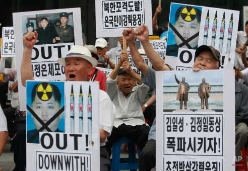 """South Korean protesters with defaced portraits of North Korean leader Kim Jong Un shout slogans during an anti-North Korean rally in Seoul, South Korea, Friday, Aug. 21, 2015. The North leader on Friday declared his frontline troops in a """"quasi-state of war"""" and ordered them to prepare for battle a day after the most serious confrontation between the rivals in years. The letters at right read: """"Explode the statues of Kim Il Sung and Kim Jong Il !"""" (AP Photo/Julie Yoon)"""