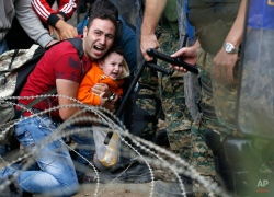 A migrant man holding a boy react as they are stuck between Macedonian riot police officers and migrants during a clash near the border train station of Idomeni, northern Greece, as they wait to be allowed by the Macedonian police to cross the border from Greece to Macedonia, Friday, Aug. 21, 2015. Macedonian special police forces have fired stun grenades to disperse thousands of migrants stuck on a no-man's land with Greece, a day after Macedonia declared a state of emergency on its borders to deal with a massive influx of migrants heading north to Europe. (AP Photo/Darko Vojinovic)