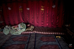 Syrian refugee Mariam Mohammed, 50, who claims that she's suffering from a chest infection, lies on a mattress inside her tents at an informal tented settlement near the Syrian border on the outskirts of Mafraq, Jordan, Tuesday, Aug. 25, 2015. (AP Photo/Muhammed Muheisen)