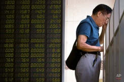 A Chinese investor monitors stock prices on a computer terminal at a brokerage house in Beijing, Tuesday, Aug. 25, 2015. China's main stock market index has fallen for a fourth day, plunging 7.6 percent to an eight-month low. (AP Photo/Mark Schiefelbein)