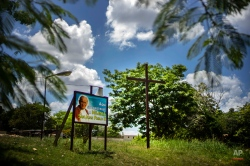 """A billboard with an image of Pope John Paul II and a message that reads in Spanish; """"Here is where the church Pope John Paul II is being built, """"stands next to a wooden cross on a field, on the outskirts of Havana, Cuba, Wednesday, Aug. 19, 2015. Cubans have begun preparations to welcome Pope Francisco in September. (AP Photo/Ramon Espinosa)"""