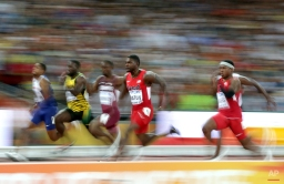United States' Justin Gatlin, centre, races in a men's 100m semifinal at the World Athletics Championships at the Bird's Nest stadium in Beijing, Sunday, Aug. 23, 2015. (AP Photo/Lee Jin-man)