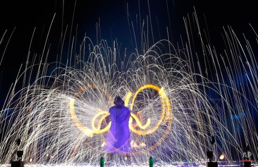 """Long exposure photo shows fire spinners whirling fire as they take part in a two-day Fire Festival """"Miff-2015"""" in outskirts of Minsk, Belarus, late Friday, Aug. 21, 2015. (AP Photo/Sergei Grits)"""