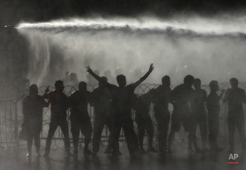 """Lebanese activists are sprayed by riot police using water cannons, during a protest against the ongoing trash crisis, in front of the government house, in downtown Beirut, Lebanon, Wednesday, Aug. 19, 2015. Lebanon's health minister says the country is on the brink of a """"major health disaster"""" unless an immediate solution is found for its mounting trash problem. Garbage has been collecting on the streets in Lebanon for the past month amid government paralysis and inability to agree on a solution after Beirut's main landfill was closed down. (AP Photo/Hussein Malla)"""