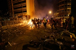 Lebanese protesters set fire to barriers and trash behind the barbed wire separating them from the police, during a protest against the trash crisis and government corruption, in downtown Beirut, Lebanon, Tuesday, Aug. 25, 2015. The powerful Lebanese Shiite group Hezbollah threw its weight behind mass protests calling for the government's resignation Tuesday, deepening a crisis that started over trash collection but is tapping into a much deeper malaise. (AP Photo/Hassan Ammar)