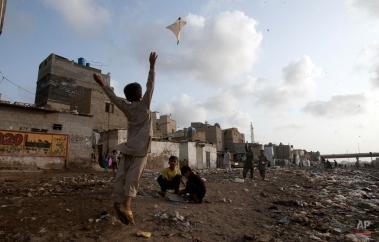 Pakistani children fly a kite in poor neighborhood in Karachi's slums, Monday, Aug. 24, 2015 in Pakistan. (AP Photo/Shakil Adil)