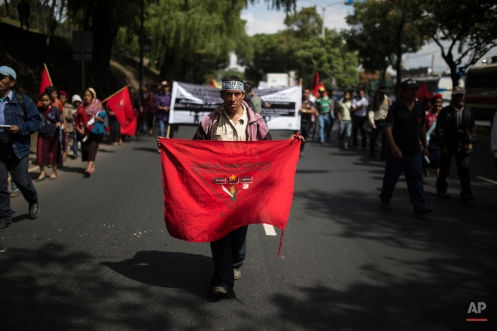 """An indigenous man holds a banner representing the Peasant Unity Committee as he takes part in a march to the National Palace to participate in a strike demanding the resignation of President Otto Perez Molina, in Guatemala City, Thursday, Aug. 27, 2015. Pressure grew Thursday on the embattled leader to resign as business and government offices closed and protesters prepared to take part in the national strike. The attorney general's office urged Perez Molina, late Wednesday, to step down """"to prevent ungovernability that could destabilize the nation."""" (Photo AP/Luis Soto)"""