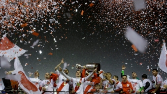 Argentina's River Plate players and staff hold the trophy aloft while they celebrate winning the the Copa Libertadores final soccer match against Mexico's Tigres in Buenos Aires, Argentina, Thursday, Aug. 6, 2015. River defeated Tigres 3-0 and became the tournament champions. (AP Photo/Ivan Fernandez)