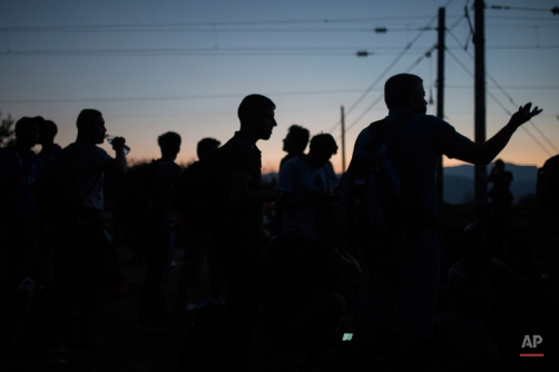 Syrian refugees wait at the border railway station of Idomeni, northern Greece, in order to be allowed by the Macedonian police to cross the border from Greece to Macedonia, Monday, Aug. 24, 2015. Thousands of migrants have arrived on Greek islands so far this year, hoping to head north to other more prosperous European countries such as Germany, the Netherlands and Scandinavian countries. (AP Photo/Santi Palacios)