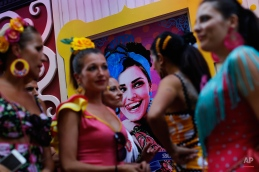 Women dressed in Spanish flamenco style clothes, gather outside a pub during local festivities in Almeria, southeast Spain, Tuesday, Aug. 25, 2015. During summer time across south Spain there are many local festivities where locals and tourists enjoy the outdoors due to the warm weather. (AP Photo/Francisco Seco)