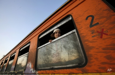 A young migrant woman from Syria looks from a window onboard a train towards Serbia, at the new transit center for migrants on the border with Greece, near southern Macedonian town of Gevgelija, on Monday, Aug. 24, 2015. Thousands of migrants have poured into Macedonia and board trains and busses that are taking them a step closer to the European Union. Police are letting the migrants pass across the border Monday, directing them to the new transit center for migrants near the border line. (AP Photo/Boris Grdanoski)