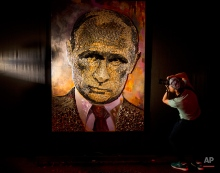 """A photographer take a photo of a portrait of Russian President, Vladimir Putin, made by Ukrainian artist Dasha Marchenko, out of cartridge cases, during a presentation in an art gallery in Kiev, Ukraine, Tuesday, Aug. 25, 2015. The installation was made of some 5,000 cartridge cases of different caliber for different types of weapons used on the firing line in the country's east, hit by conflict with pro-Russian separatists. Marchenko explained that the 2.4 x 1.7 meter painting, that she called """"The Face of War"""" had been created in response to recent events in Ukraine. (AP Photo/Efrem Lukatsky)"""