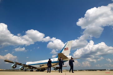 Military personnel hold their hats as Air Force One, with President Barack Obama aboard, departs from Andrews Air Force Base, Md., Monday, Aug. 24, 2015, en route to Las Vegas, Nev. where the the President will speak at the National Clean Energy Summit. (AP Photo/Jose Luis Magana)