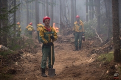 Firefighters extinguish flames from a wildfire near Turka in Siberia, Russia, Friday, Aug. 28, 2015. There are reports of spreading forest fires in Siberia. (AP Photo/Anna Ogorodnik)