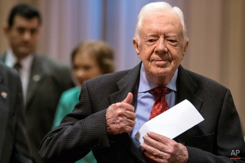 """Former President Jimmy Carter walks to a news conference followed by his wife, Rosalynn Carter, center, at The Carter Center in Atlanta on Thursday, Aug. 20, 2015. Carter announced that his cancer is on four small spots on his brain and he will immediately begin radiation treatment, saying he is """"at ease with whatever comes."""" (AP Photo/Ron Harris)"""