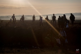 Syrian refugees walk among fields at the border town of Idomeni , northern Greece to cross the border and enter Macedonia, on Tuesday Aug. 25, 2015. The U.N.ís refugee agency said it expects 3,000 people to cross Macedonia daily in the coming days. Greece has been overwhelmed this year by record numbers of migrants who have been arriving on a number of Greek islands.(AP Photo/Santi Palacios)