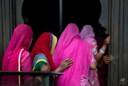 Indian women devotees stand in a queue as they wait to enter a temple near the Godavari River during Kumbh Mela, or Pitcher Festival, in Nasik, India, Friday, Aug. 28, 2015. Millions of Hindu pilgrims are expected to attend this year's two-month festival, which began in mid-July and runs until the end of September. During the festival pilgrims take dips in the waters of a holy river as part of a ritual, believed to cleanse them of their sins. (AP Photo/Tsering Topgyal)