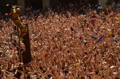 A hooded man with a colorful outfit known as the 'Cipotegato' acknowledges the crowd after running through the streets of Tarazona, Spain, Thursday, Aug. 27, 2015. Following a tradition coming from at least the middle of the XVIII century, thousands of people gather every year at midday in Tarazona's main square waiting to throw tomatoes to the Cipotegato character, that represents a prisoner from the local jail that was given the chance to escape to freedom after crossing through a crowded village. (AP Photo/Alvaro Barrientos)