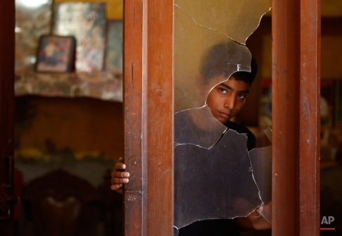 An Indian boy looks outside a glass window damaged in alleged firing from the Pakistan side into a residential area at Sai village, in Ranbir Singh Pura near the India-Pakistan international border, about 40 kilometres (25 miles) from Jammu, India, Friday, Aug. 28, 2015. Indian and Pakistani border guards traded gunfire in the divided region of Kashmir, striking homes at villages near the disputed border region after midnight. (AP Photo/Channi Anand)