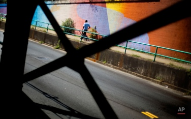 A pedestrian passes a mural along the Boulevard tunnel Tuesday, Aug. 25, 2015, in Atlanta. More than 1,000 feet of walls in the tunnel were painted last year in bright colors as part of an effort by Living Walls, an organization that brings artists together to create murals in the city's public spaces. (AP Photo/David Goldman)