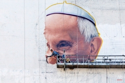 A sign painter outlines the Pope's nose on the side of a New York City office building, Thursday, Aug. 27, 2015. Pope Francis visits the U.S. beginning Sept. 22 with stops in Washington D.C., New York and Philadelphia. (AP Photo/Mark Lennihan)