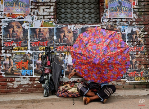 A Bangladeshi man fixes an umbrella as he sits in front of the posters of a film ìRana Plazaî pasted on the wall of a movie theatre in Dhaka, Bangladesh, Tuesday, Aug. 25, 2015. Bangladesh's High Court has imposed a six-month ban on the screening of the movie about a garment worker who was rescued from the rubble 17 days after a five-story factory complex collapsed more than two years ago, killing more than 1,000 people. (AP Photo/A.M. Ahad)