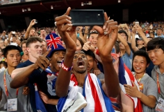 Britain's Mo Farah has a selfie taken with spectators as he celebrates after winning the gold medal in the men's 5000m final at the World Athletics Championships at the Bird's Nest stadium in Beijing, Saturday, Aug. 29, 2015. (AP Photo/Ng Han Guan)