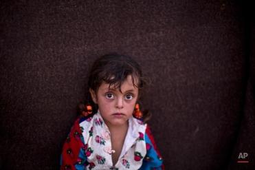 Syrian refugee girl Zahra Mahmoud, 4, sits in front of her family's makeshift tent at an informal tented settlement near the Syrian border on the outskirts of Mafraq, Jordan, Wednesday, Aug. 19, 2015. (AP Photo/Muhammed Muheisen)