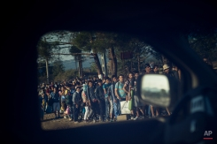 Migrants are seen through the window of a police car at the Greek-Macedonian border, as they wait to be allowed by Macedonian police to cross the border, Idomeni, northern Greece, Thursday, Aug. 27, 2015. Thousands of migrants have arrived on Greek islands so far this year, hoping to head north to other more prosperous European countries such as Germany, the Netherlands and Scandinavian countries. (AP Photo/Santi Palacios)
