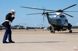A Marine holds on to his hat as the Marine One helicopter takes off to take President Barack Obama to the White House on return to Washington from Las Vegas, after Air Force One landed at Andrews Air Force Base, Md., Tuesday, Aug. 25, 2015. (AP Photo/Jacquelyn Martin)
