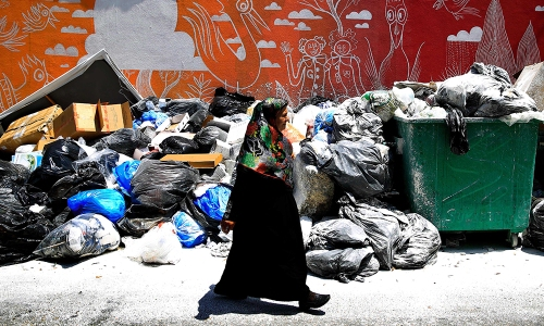 A Lebanese woman passes by a pile of garbage on a Beirut street, Lebanon, Tuesday, July 21, 2015. Garbage is piling up on the streets of Beirut amid a growing dispute over tiny Lebanon's largest trash dump. (AP Photo/Hassan Ammar)